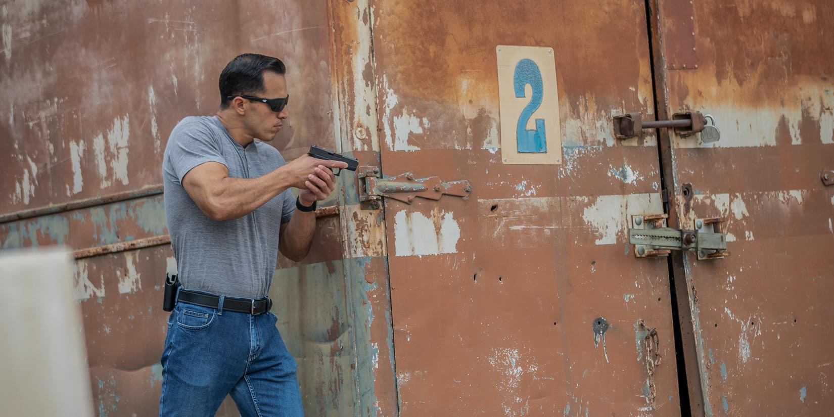 Man next to rusty shipping container with a Safariland holster