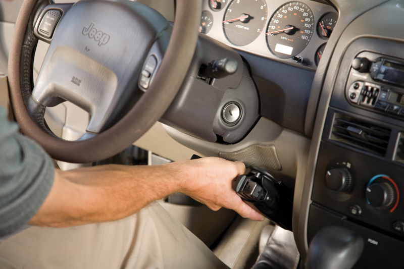Safariland® holster attached under a car steering wheel using the Quick Locking System (QLS).