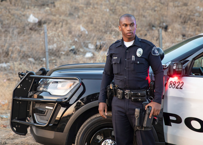 Police officer next to his patrol vehicle wearing a Safariland® duty holster.